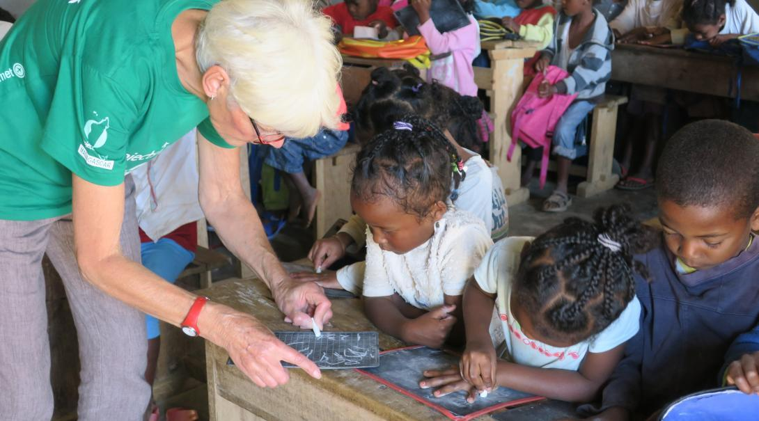 An older volunteer abroad works with children at an Early Childhood Development Centre in Madagascar.